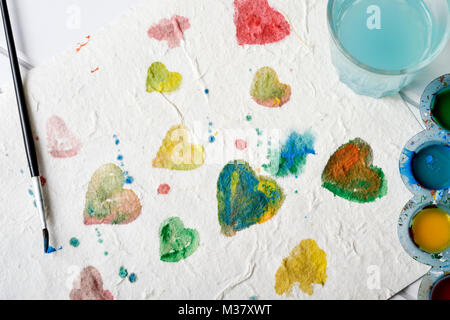 high angle view of a piece of paper with some hearts of different colors painted by myself with watercolor paint, - Stock Photo