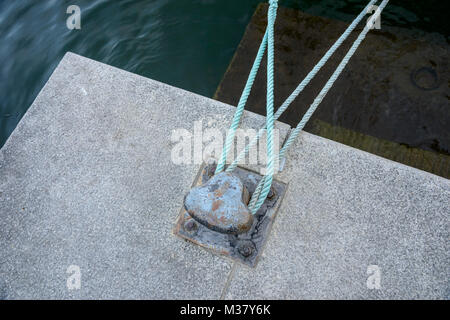 Ropes tying boat to iron dock bollard - Stock Photo