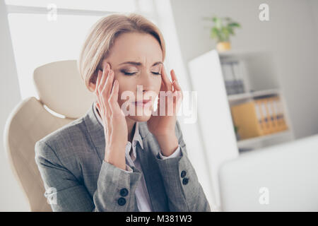 Pretty, attractive, mature, adult, middle age woman in classic outfit sitting on armchair in workplace, workstation, - Stock Photo