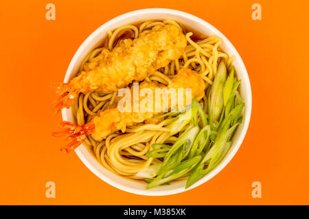 Japanese Style Tiger Prawn Tempura Noodle Soup With Spring Onions Against An Orange Background - Stock Photo