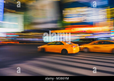 New York City - March 21, 2017 : Yellow taxi cab speeds down in a New York City Street. Shot with long shutter speed - Stock Photo