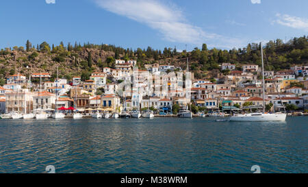 Waterside view on Poros town with white houses, moored sailing yachts and forested hill - Stock Photo