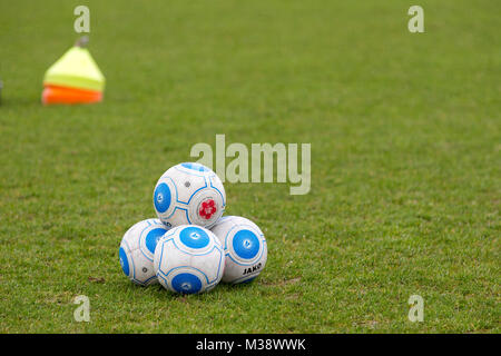 Jako footballs piled up on a football pitch prior to a National League match with training cones in the background