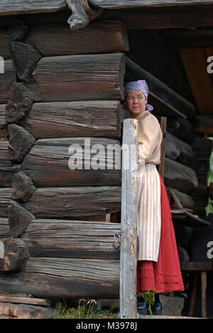Young woman in old traditional dress at the entrance of a wooden house, Skansen Open-Air Museum, Stockholm, Sweden - Stock Photo