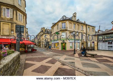 The one way Rue Saint-Jean, the main street full of cafes and shops in the Normandy city of Bayeux, France with - Stock Photo
