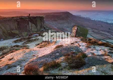 A photographer stands at dawn on frost covered Curbar Edge in winter, near Calver, Peak District National Park, - Stock Photo