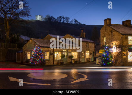 Shops in Castleton at Christmas backed by Peveril Castle at night, Peak District National Park, Derbyshire, England, - Stock Photo