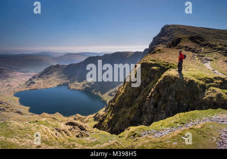 Walker looking out over Llyn Cau from Craig Cau, Cadair Idris, Snowdonia National Park, North Wales, UK MODEL RELEASED - Stock Photo