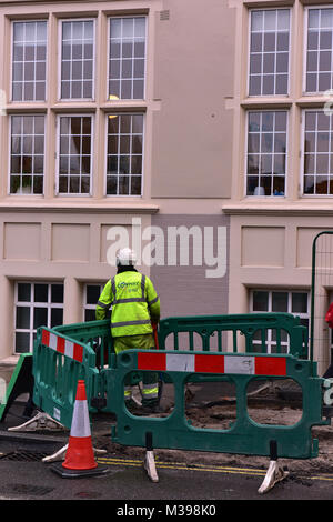 a road closure due to roadworks in central london with a workman in yellow high visibility clothing standing next - Stock Photo