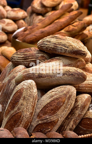 a selection of freshly baked bread rolls and artisan bakery items on sale at a bakers shop or stall at borough market - Stock Photo
