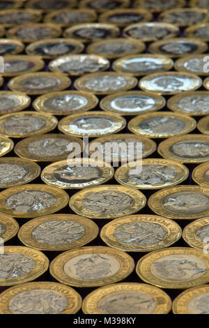 A large number of one pound coins or 1 pounds laying on a flat surface in gold and silver cash or money. Ready cash - Stock Photo