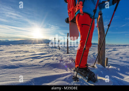 Closeup of snowboarder walking on snowshoes in powder snow. European Alpine scenery, winter sports and activities - Stock Photo