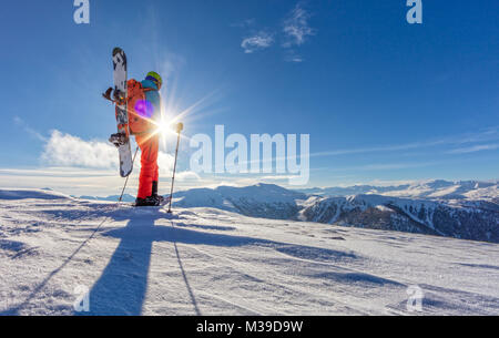 Snowboarder walking on snowshoes in powder snow. European Alpine scenery, winter sports and activities - Stock Photo