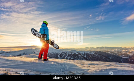 Snowboarder on the top of mountain, ready to downhill run off piste. European Alpine scenery in sunset light - Stock Photo
