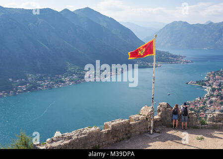 Montenegrin flag on the top of Saint John Fortress ruins above Kotor coastal city, located in Bay of Kotor of Adriatic - Stock Photo