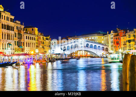 View of the Rialto Bridge and Grand Canal in Venice at night. - Stock Photo