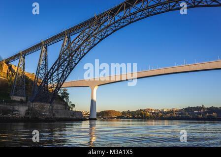 Old Maria Pia Bridge and new railway bridge of Saint John over Douro River between Porto and Vila Nova de Gaia city - Stock Photo