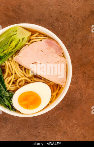 Bowl Of Japanese Style Pork Ramen Noodle Soup With Pak Choi And A Boiled Egg Against A Red Tiled Background - Stock Photo