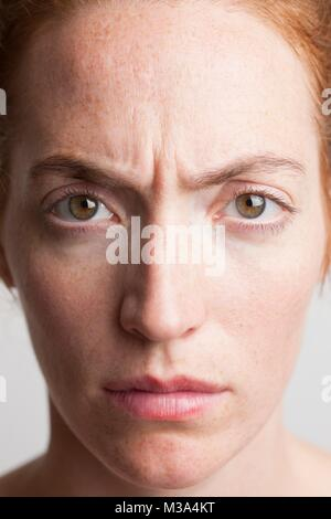 MODEL RELEASED. Close-up of young woman looking angry. - Stock Photo