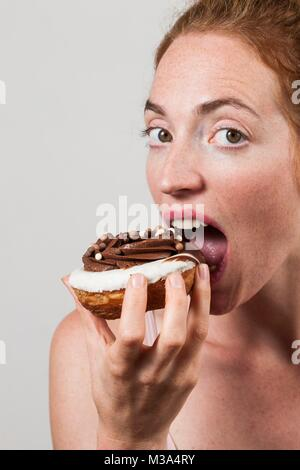 MODEL RELEASED. Close-up of woman eating chocolate doughnut. - Stock Photo