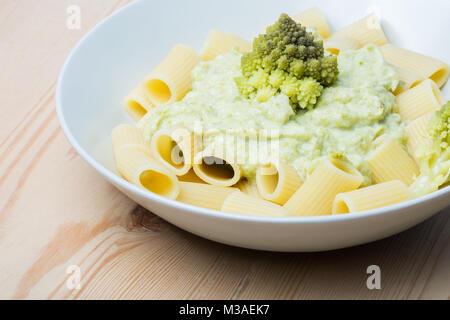 Pasta with Romanesco broccoli cabbage and mozzarella. On rustic background. - Stock Photo