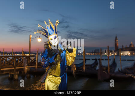 Venice, Italy 10th February, 2018. People in costumes and masks pose at dawn during a beautiful sunrise near St - Stock Photo