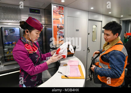 Chongqing. 10th Feb, 2018. An attendant checks the meal which Zhang Yuliang ordered on cellphone on train G8516 - Stock Photo