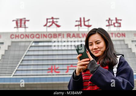 (180210) -- CHONGQING, Feb. 10, 2018 (Xinhua) -- Zhang Yuliang checks ticket information on her cellphone at the - Stock Photo