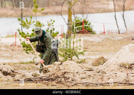 A German soldier of the Second World War digs a trench. Reconstruction of the liberation of the city of Gomel - Stock Photo