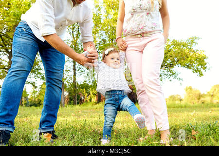 The first steps of the baby. Parents are teaching their child to - Stock Photo