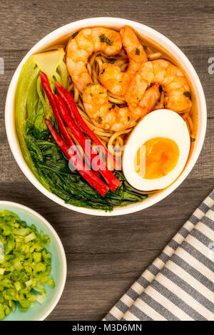 Japanese Style Prawn And Noodle Ramen Soup With Pak Choi And Chillies On A Dark Wooden Table - Stock Photo