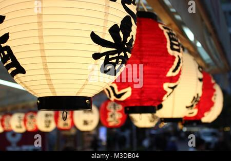 Red and white Japanese paper lanterns  hanging from the ceiling - Stock Photo