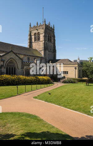 Under a deep blue sky, an exterior view of Bradford Cathedral with its squat, square tower & peaceful gardens - - Stock Photo