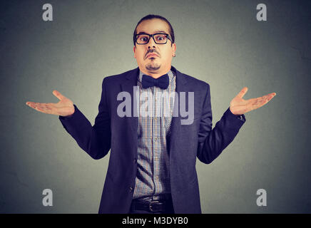 Young man in formal clothing shrugging shoulders while posing on gray and looking confused. - Stock Photo
