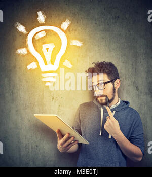 Casual young student using tablet and creating new idea looking up. - Stock Photo