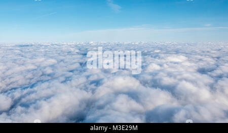 White Dense Cloud Covering with Blue Open Skies Above - Stock Photo