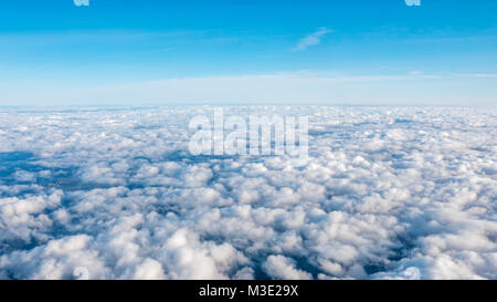 Aerial View of Clouds Covering to the Horizoin with City peeking through - Stock Photo