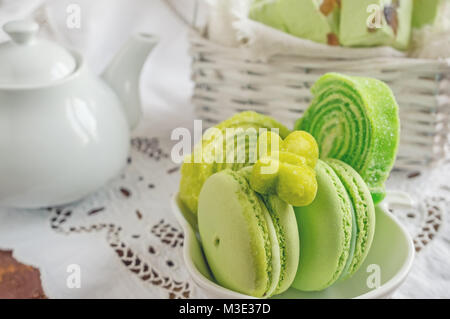 Freshly baked colored macaroons in wicker basket with handles with small white flowers on wooden background. Selective - Stock Photo