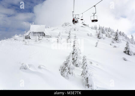 Double seat lift above snow covered hill with pine trees and cabins, Velika Planina, Slovenia. - Stock Photo