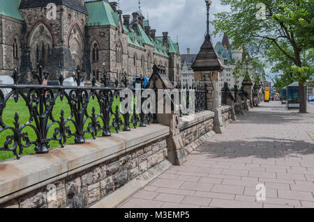 Sidewalk in Ottawa, Ontario Canada with black wrought iron fence above a stone wall barrier on the side - Stock Photo