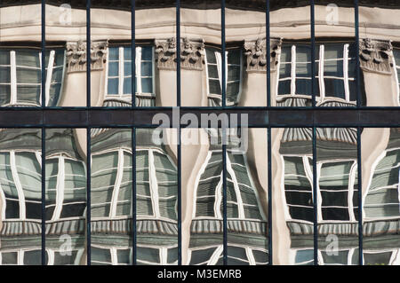 warped reflection of old building in windows of new glass front modern building - Stock Photo