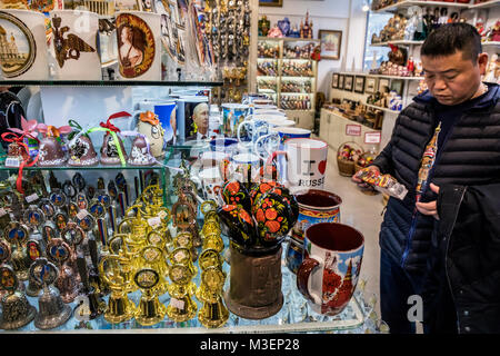 Chinese tourist selects souvenirs in a souvenir shop on Nikolskaya street in the center of Moscow, Russia - Stock Photo