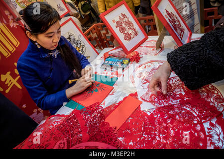 A chinese master is engaged in Jianzhi folk art - traditional folk decorative Chinese paper cutting - Stock Photo
