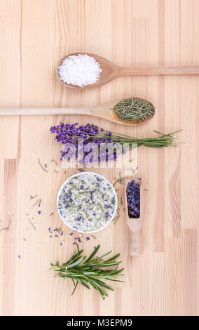 Top view of seasoned salt with rosemary and lavender blossoms  on a wooden background - Stock Photo
