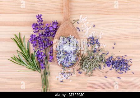 top view of a spoon with herbal salt of rosemary and lavender blossoms on a wooden background - Stock Photo