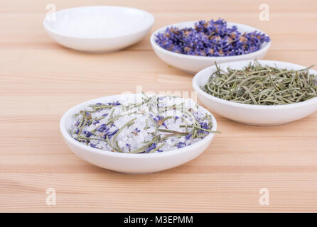 Herbal salt with rosemary and lavender blossoms on a wooden background - Stock Photo