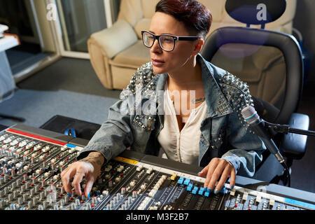 Pensive sound director using audio mixer in studio - Stock Photo
