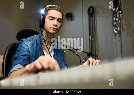 Concentrated music engineer working on sound mixer - Stock Photo