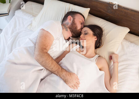 a man and a woman sleeping in beds at home - Stock Photo
