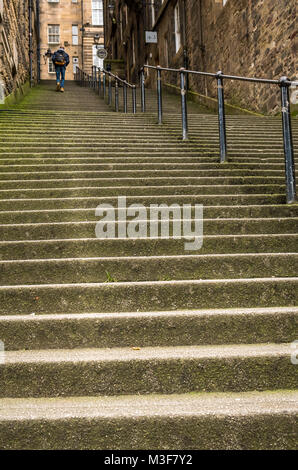 Man walking up steep stone steps in an alley or narrow passage, Warriston's Close, Cockburn Street, Edinburgh, Scotland, - Stock Photo